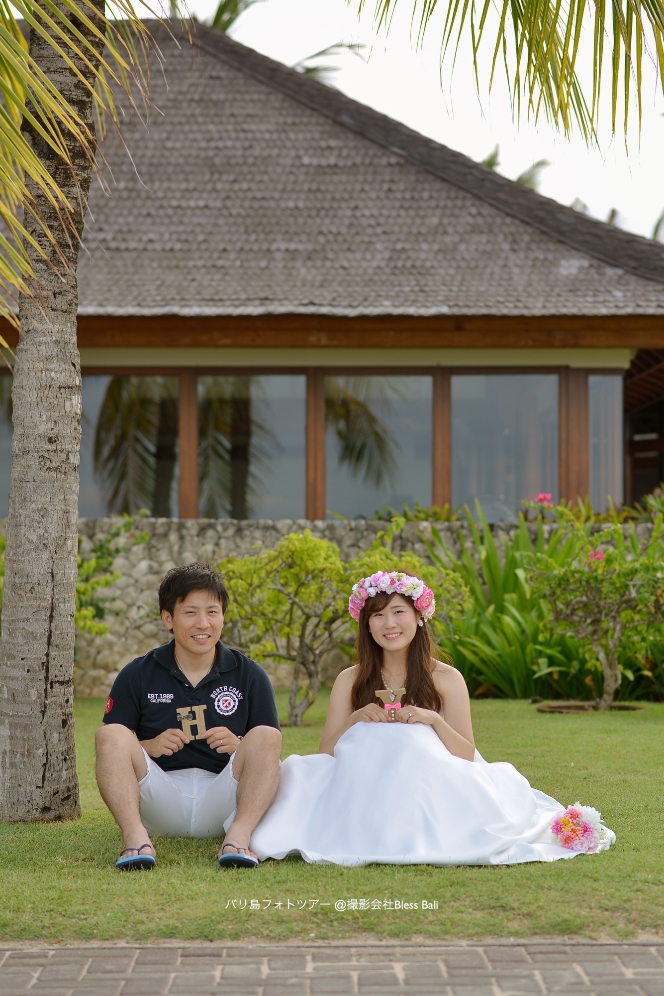 バリ島ガーデンエリアで座って微笑む新郎新婦