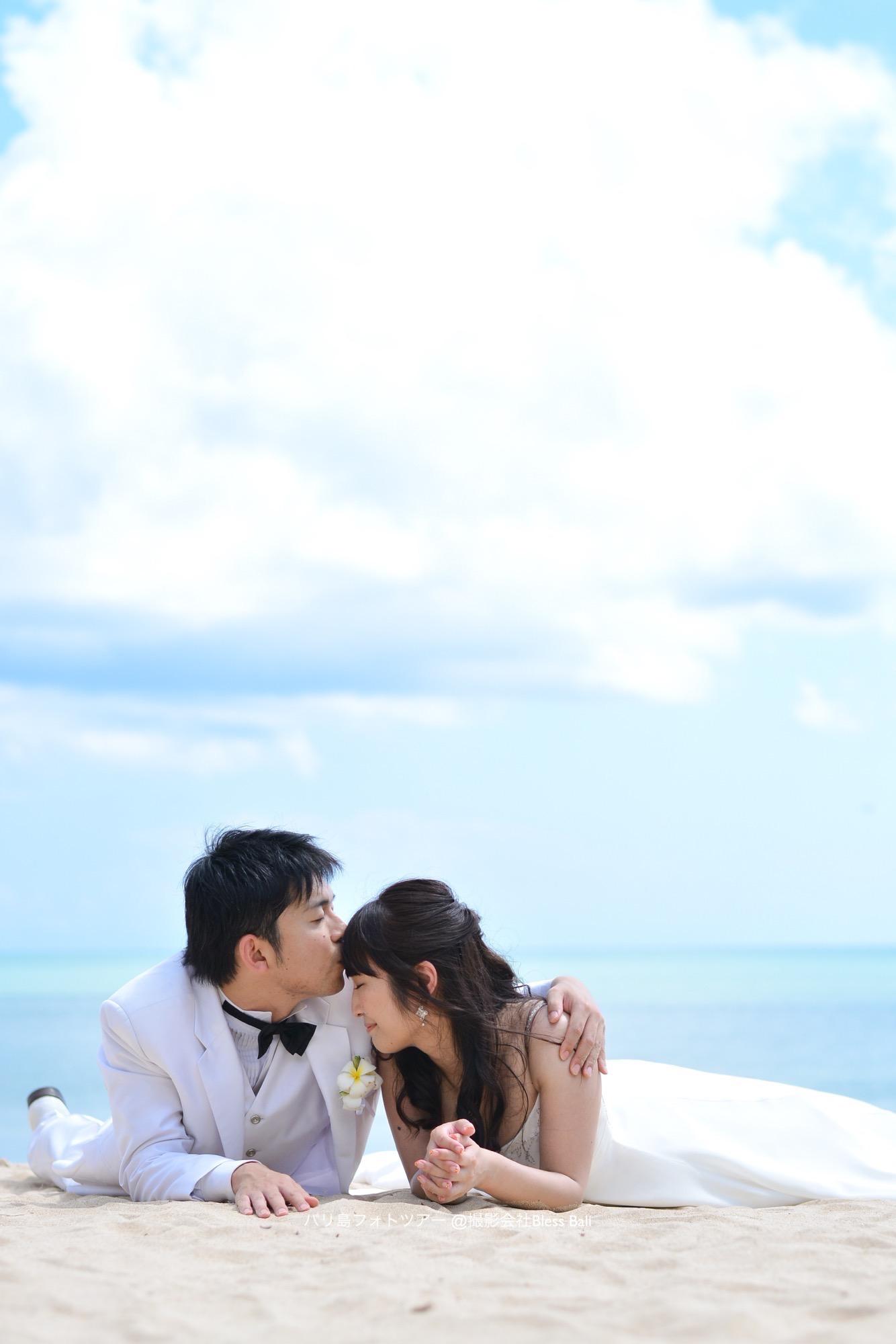 砂浜に寝そべって花嫁のおでこにキスする花婿