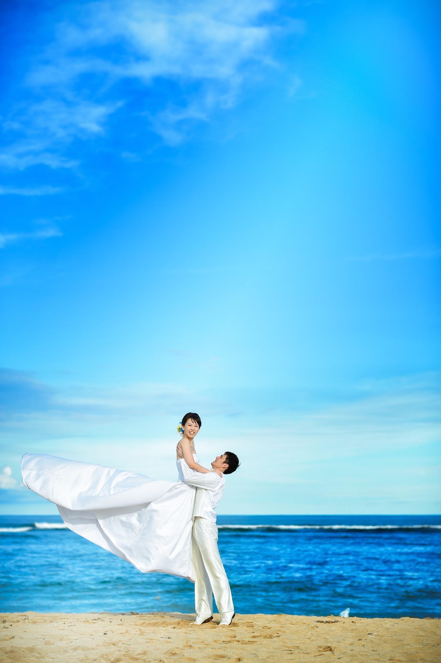 ホテル前のビーチで花嫁を抱き上げる花婿