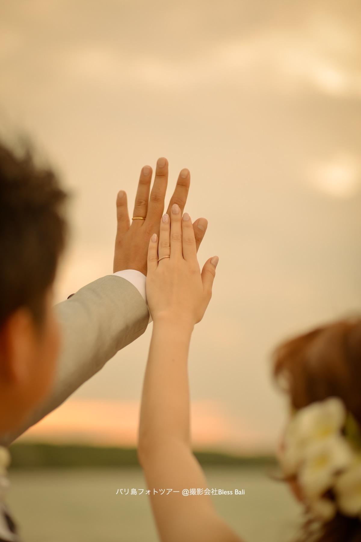 大切な結婚指輪を空に掲げて