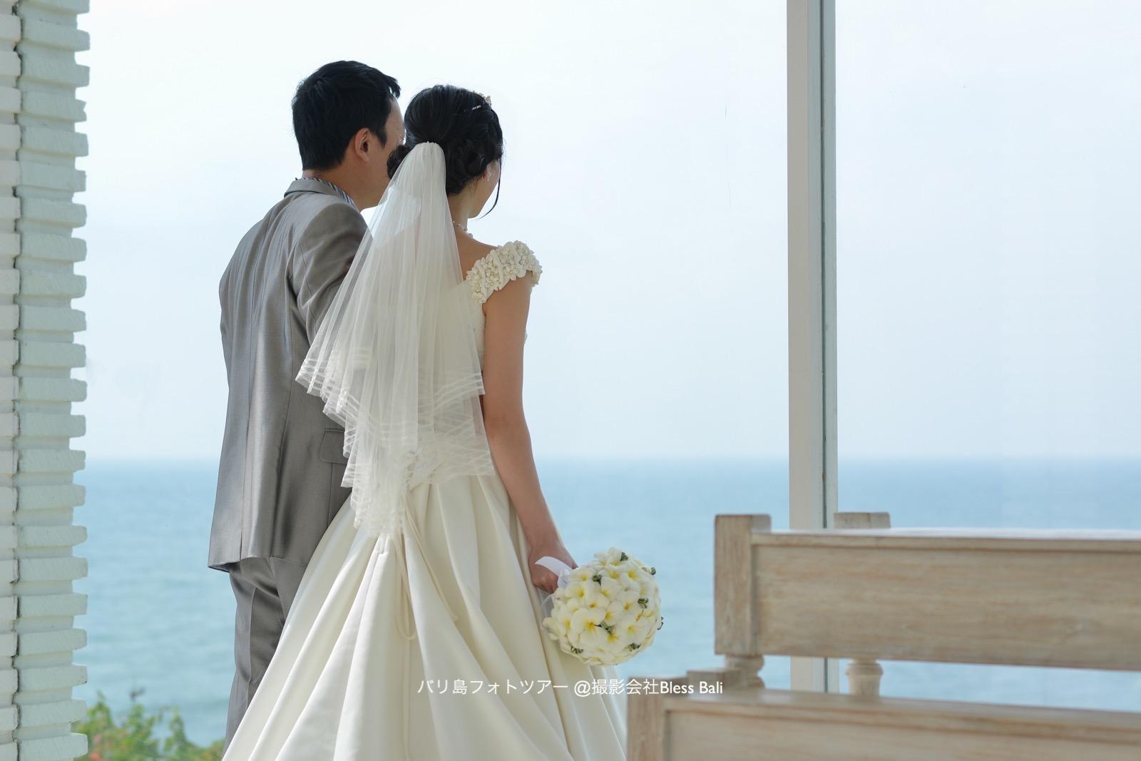 チャペルから海を眺める新郎新婦