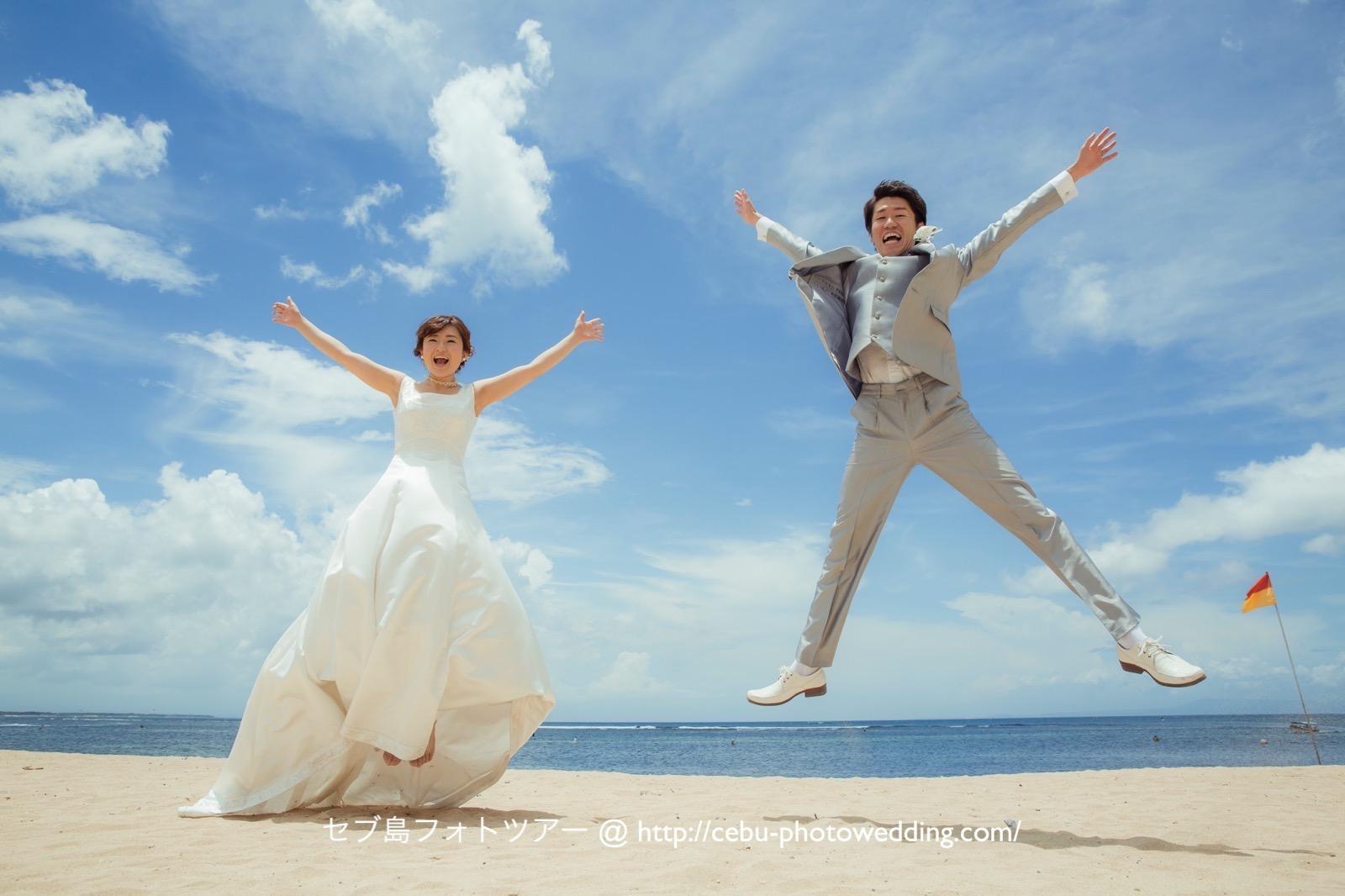 晴れた青空の下で新郎新婦が笑顔でジャンプ